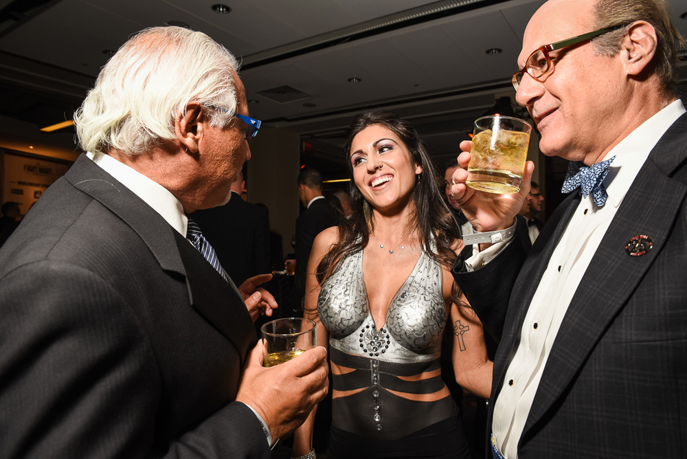 Medstar Georgetown University Hospital Board Chairman S. Joseph Bruno (left) and attorney Anthony Cantalupo enjoy the charms of body paint model Sofia Schramm. Female performers and cocktail waitresses sported elicit black tie body paint and elaborate costumes during the cocktail reception.