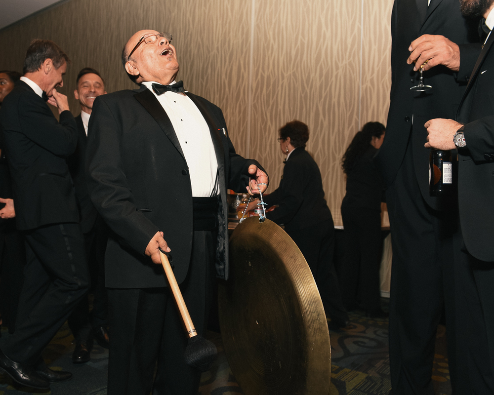 Lolo Villagomez strikes the gong that signals to guests that dinner is served in the ballroom. To his right is a guest that was almost 8 feet tall.