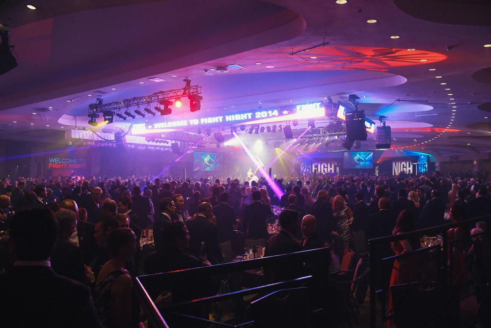 Tuxedo-clad men mill around the smoke-drenched Washington Hilton ballroom. 2,000 business leaders and government officials attend the annual fundraiser event, which raises millions for DC children's education and healthcare.