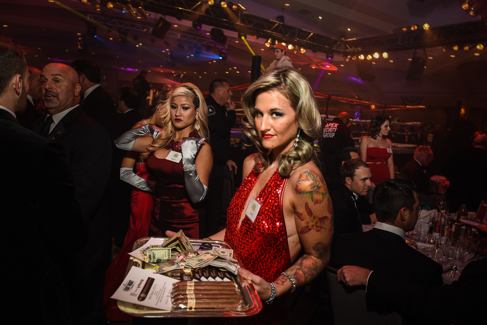 Cocktail waitress Dana Nelson takes a spin around the ringside sponsor tables with a tray of cash and cigars for sale to benefit Fight for Children.