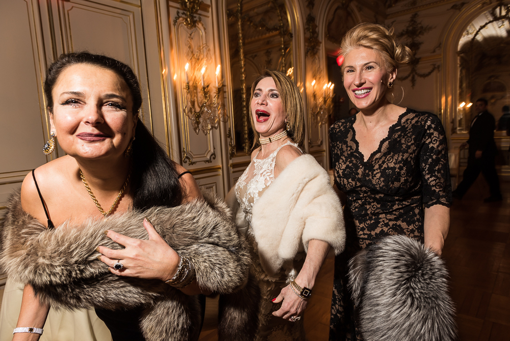 Diplomatic Liaison Rhoda Septilici, left, clutches her fur as she laughs with her friends, Leila Beale, wife of the Barbados ambassador (center), and Gabriela Coman (right) at the Russian Ball.
