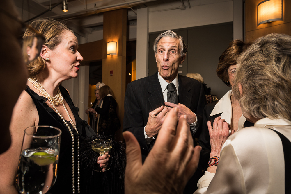 Guests at the gala wear attired in black and white creative black tie tailored to the 1920s theme. Bob Tracy, center, reacts animatedly to a story told by Janet Wittes (far left) as Christine Hollins (second from left) looks on and Marty Gross and Toni Ritzenberg chat nearby.