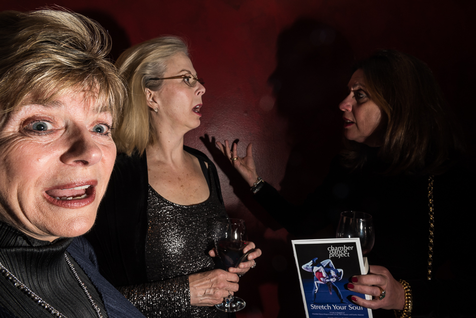 Herta Felly looks excitedly toward the theater as the hosts announce the beginning of the performance portion of the gala, as Elizabeth Patton and Farida Wozniak chat nearby.