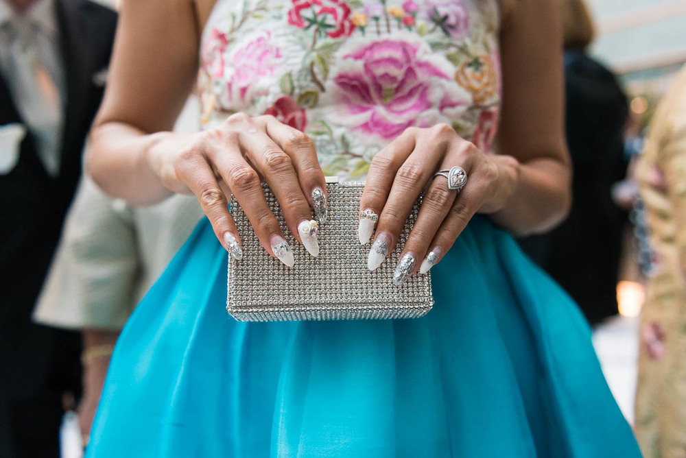 Sunghee Thomson shows off her edgy manicure and rhinestone box clutch that complement her embroidered top and ball skirt.