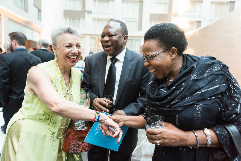 The South African Ambassador Mninwa Mahlangu, center, and his wife Nomaswazi exclaim over the African bracelet worn by Njambi, the Embassy Adoption Program Coordinator at the Washington Performing Arts during the organization's international gala on May 2.