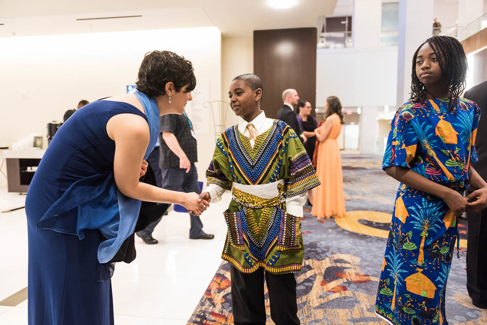 Embassy Adoption Program manager Kayla Gatalica shakes hands with Johnnie Mac, one of the DCPS students who performed.