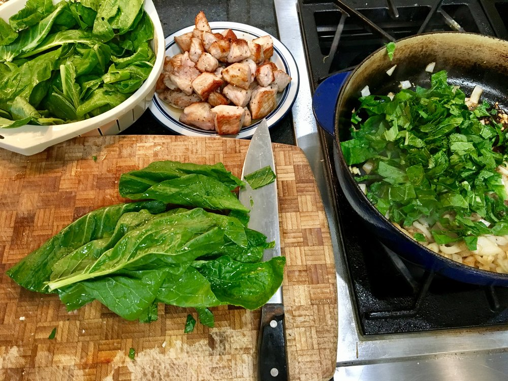 Adding chopped mustard greens to the mix.