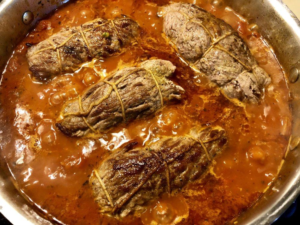 Braciole braised in tomato sauce.