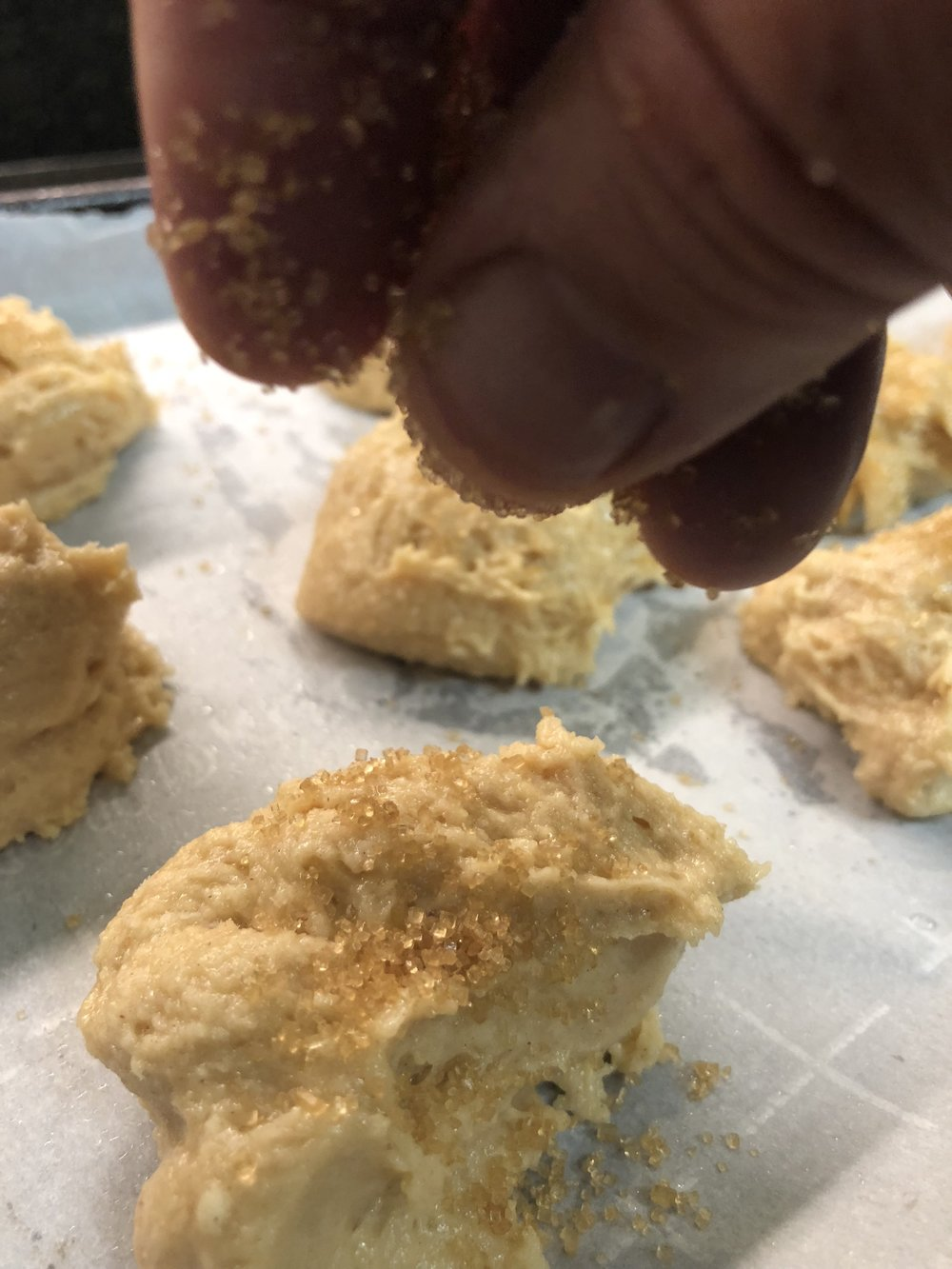 Sprinkling the tops of the spiced shortbread with crunchy turbinado sugar.