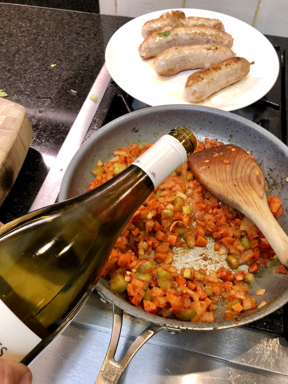 Deglazing the pan of  mirepoix  and tomato with dry white wine
