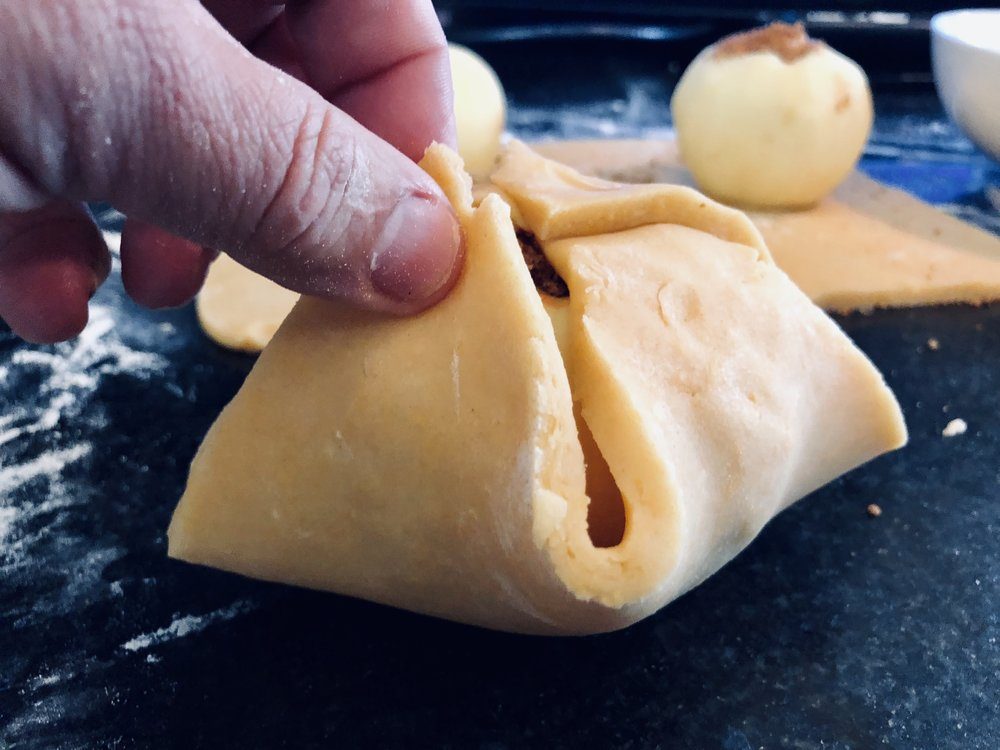 Bring up each corner of the pastry and pinch the seams closed.