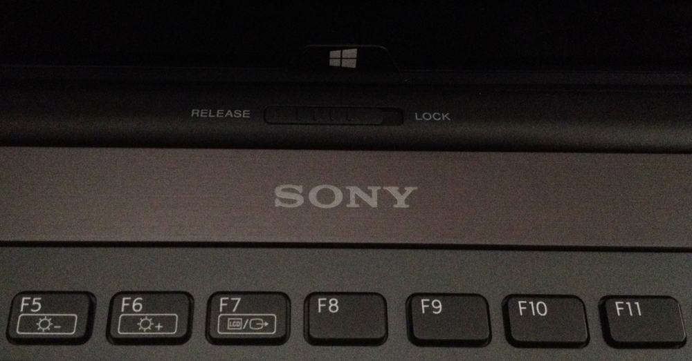 The  switch at the top of the keyboard releases or locks the screen in place.