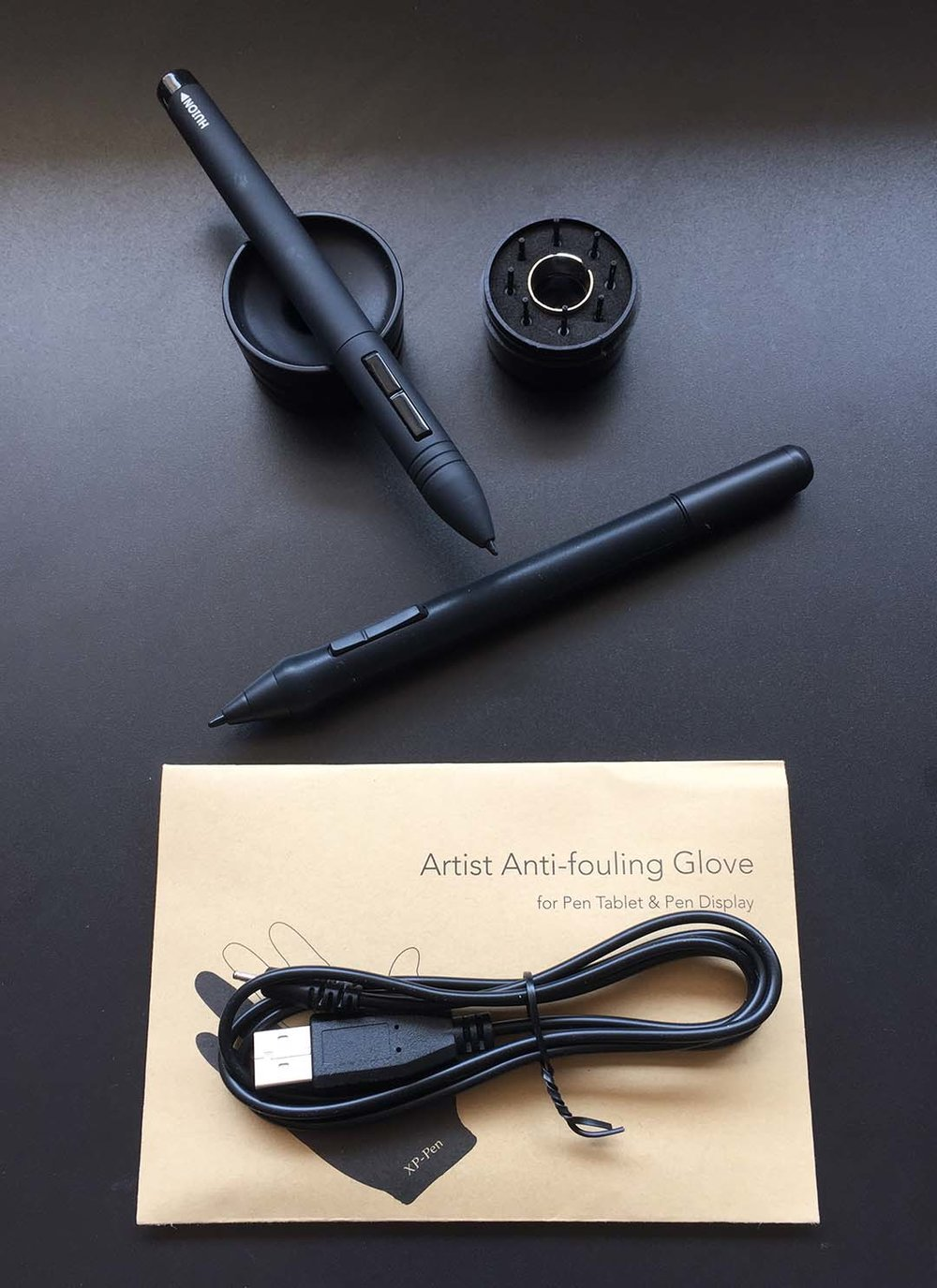 The Artist 16 ships with two pens, a pen holder, eight spare nibs, and artist's glove among several other accessories and cables. The top pen pictured above is the compatible Huion GT-220 pen.