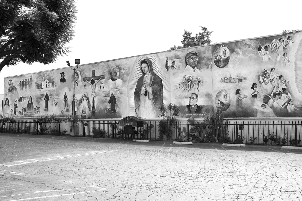 """Hope,"" a mural by Miguel Ramirez depicting Catholic religious figures, Black civil rights leaders, and images of Central American political struggles, St. Lawrence of Brindisi Church, Watts, South Los Angeles. In recent years, Irish pastor Peter Banks, who gives services in English and Spanish, has made efforts to bring together local Black and Latina/o populations, in particular those who live in the nearby Nickerson Gardens housing projects. According to the artist, the mural, completed in 2000, was intended to bring the people of Compton ""hope and dreams"" at the opening of the new century. 2009. Copyright Miguel Ramirez.                                0     false             18 pt     18 pt     0     0         false     false     false                                                     /* Style Definitions */ table.MsoNormalTable 	{mso-style-name:""Table Normal""; 	mso-tstyle-rowband-size:0; 	mso-tstyle-colband-size:0; 	mso-style-noshow:yes; 	mso-style-parent:""""; 	mso-padding-alt:0in 5.4pt 0in 5.4pt; 	mso-para-margin:0in; 	mso-para-margin-bottom:.0001pt; 	mso-pagination:widow-orphan; 	font-size:10.0pt; 	font-family:""Times New Roman"";}"