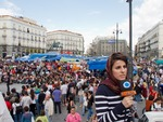 Click photo to download. Caption: Sonia Labboun, correspondent of Iranian Press TV in Puerta del Sol, Madrid, during the Spanish protests in May 2011. Credit: Kadellar/Wikimedia Commons.