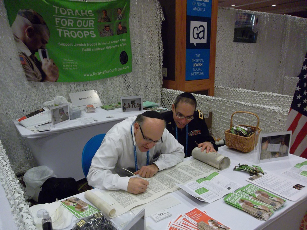 "Representatives of ""Torahs for Our Troops"" examine a Torah scroll at their GA booth in Denver. Credit: Jacob Kamaras."