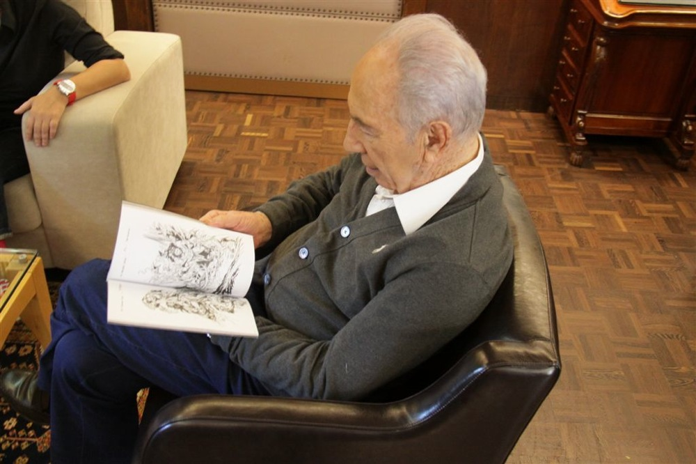 Click photo to download. Caption: President Shimon Peres reads a comic book artist Joe Kubert's work. Credit: Credit: Yosef Avi Yair Engel.