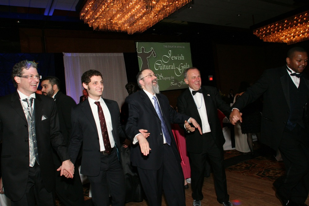 Click photo to download. Caption: Rabbi Yosef Greenberg (center), director of the Lubavitch Jewish Center of Alaska, holds hands with attendees at the center's recent Jewish Cultural Gala. Credit: Lisa J. Seifert.