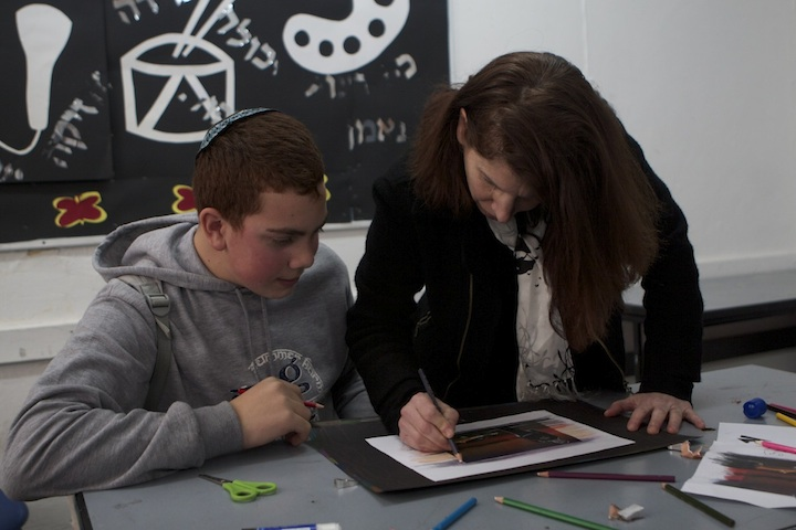 Click photo to download. Caption: Andrea Rabinovitch works with an Israeli student. Credit: Courtesy of Yeshiva University.