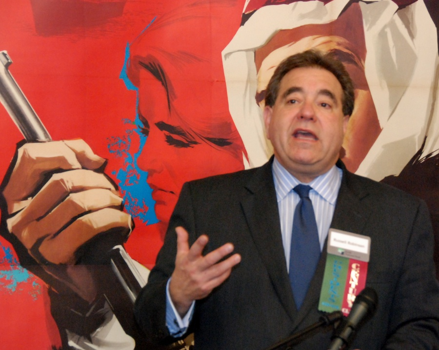 "Click photo to download. Caption: Russell Robinson, JNF CEO, welcomes visitors to the ""Made in Israel 2012"" exhibit (with one of the exhibit's posters providing a backdrop) on March 28 at the Jewish National Fund house in New York. Credit: Maxine Dovere."