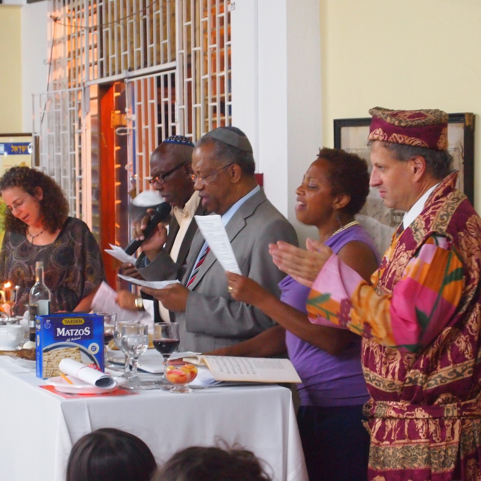 Click photo to download. Caption: Rabbi Dana Evans Kaplan (far right), dressed as Elijah, celebrates Passover with congregants of Shaare Shalom Synagogue in Kingston, Jamaica. Credit: Courtesy Rabbi Dana Evans Kaplan.
