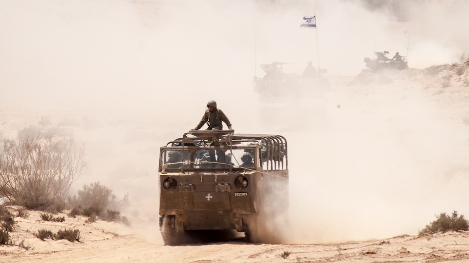 "Click photo to download. Caption: An IDF soldier hitches a ride on an ""Alfa"" transporter heading back to base after taking part a mock assault on an enemy stronghold at the Shivta Field Artillery Base, in southern Israel, Thursday, May 24, 2012. Credit: B. Davidson."