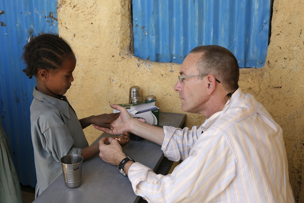 Click photo to download. Caption: Dr. Rick Hodes treats a baby in Ethiopia. Credit: Richard Lord/JDC.