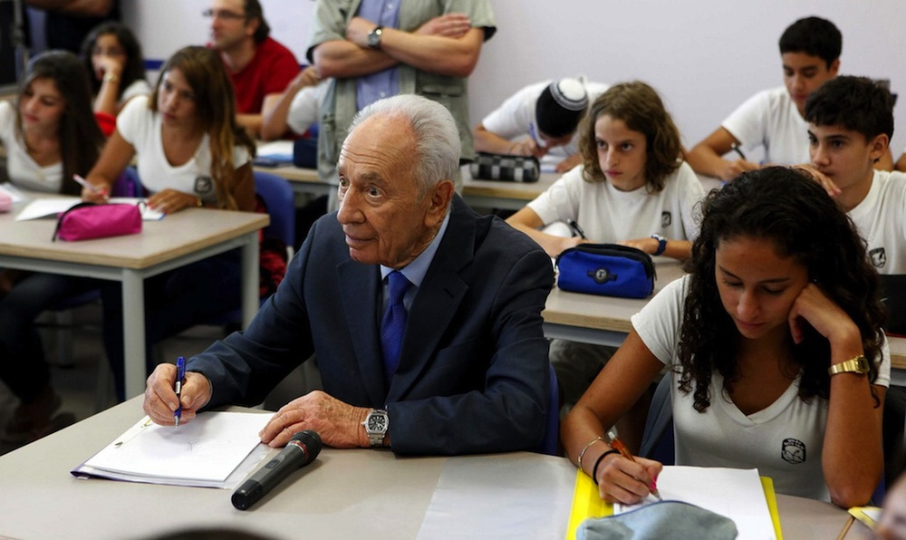 Click photo to download. Caption: Israeli president Shimon Peres sits with first graders on the first day of school in the Sha'ar Hanegev area in southern Israel on Monday, the same day a Qassam rocket was fired into the area from the Gaza Strip. Credit: Edi Israel/Flash90.