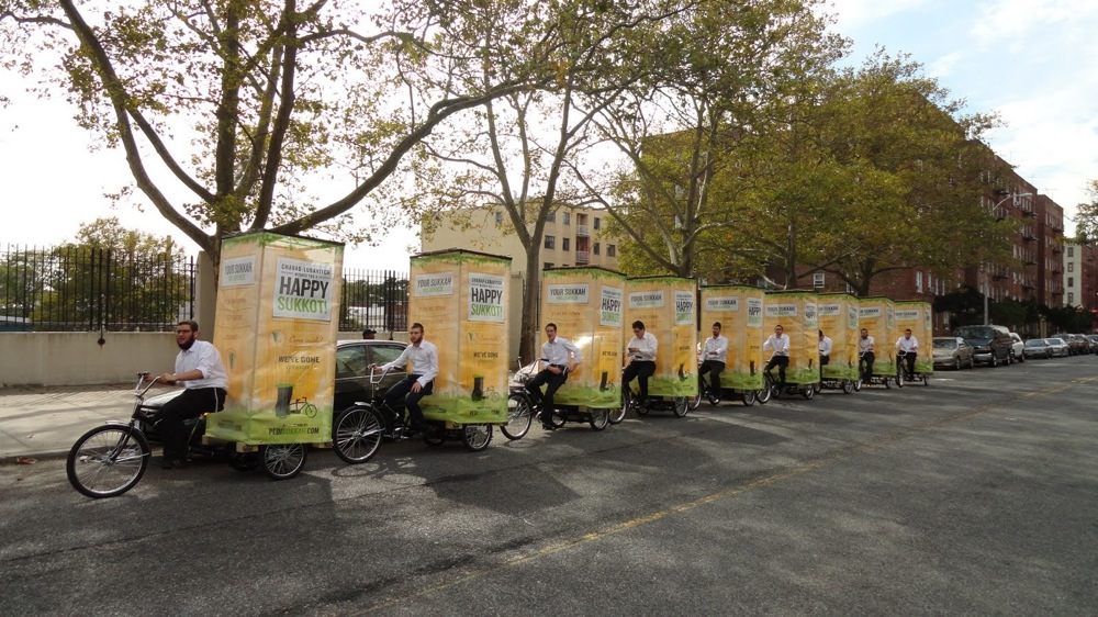 "(Click photo to download. Caption: Levi Duchman's 2011 ""PediSukkah"" fleet—nine bicycles carrying sukkahs on rickshaws—rides through New York on Tuesday, Oct. 11, 2011. Credit: Levi Duchman.)"
