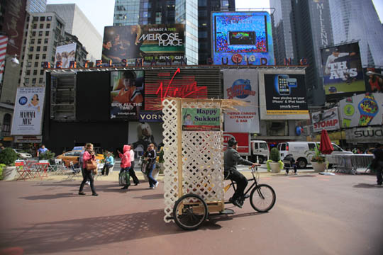 (Click photo to download. Caption: Levi Duchman pedals a sukkah through Times Square in Manhattan. Credit: Courtesy Levi Duchman.)