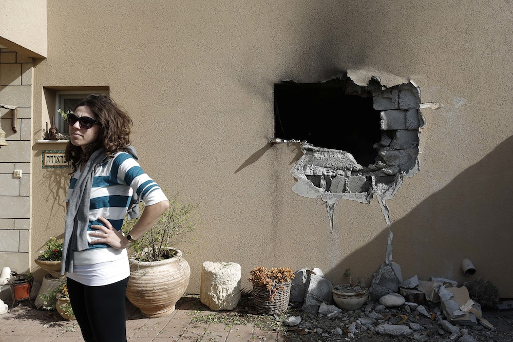 Click photo to download. Caption: An Israeli woman stands outside a damaged house hit by a rocked fired from the Gaza Strip that hit a house near the Israel-Gaza border, Friday, Nov. 16, 2012. Credit: Tsafrir Abayov/Flash90.
