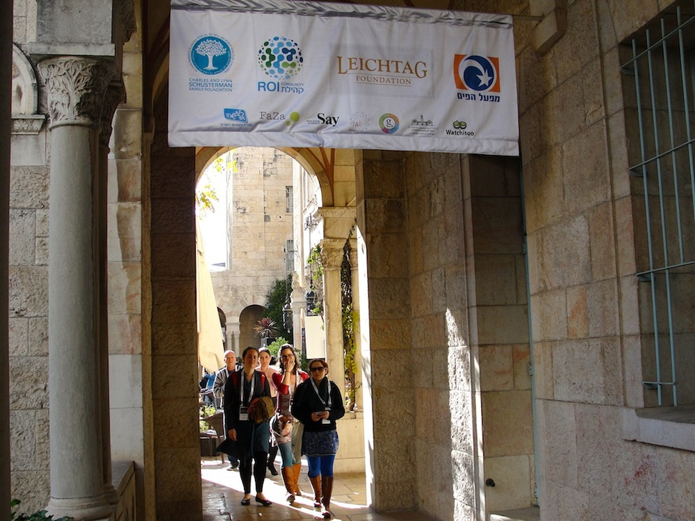 Click photo to download. Caption: Attendees of the TEDx conference walk in the Jerusalem YMCA under a poster featuring conference sponsors. Credit: Judy Lash Balint.