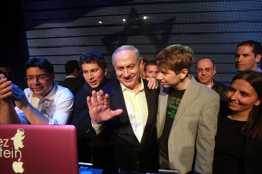 Click photo to download. Caption: Prime Minister      Binyamin Netanyahu, together with his children, waves to young supporters from behind the DJ's station in a Tel Aviv nightclub on Jan. 6, 2013, calling for the public to support the Likud Beiteinu party. Credit: Yossi Zamir/Flash 90.