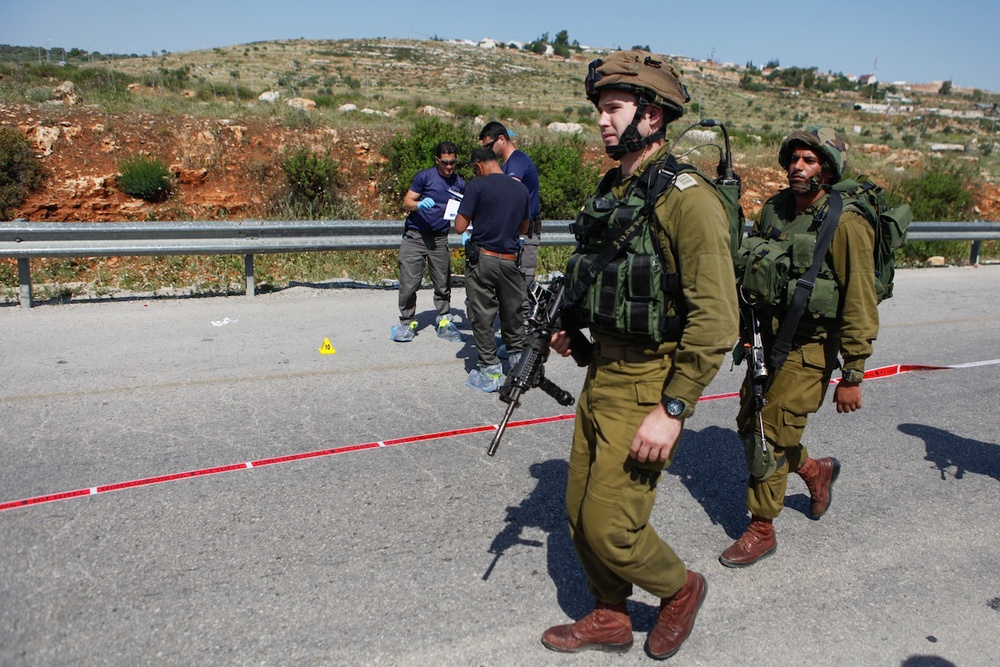 Click photo to download. Caption: Israeli security forces inspect the site of a terror attack, at a bus stop at the Tapuach Junction on April 30, 2013. The Palestinian terrorist stabbed a 31-year-old Israeli man to death at a bus stop, police said. Credit: Flash90.