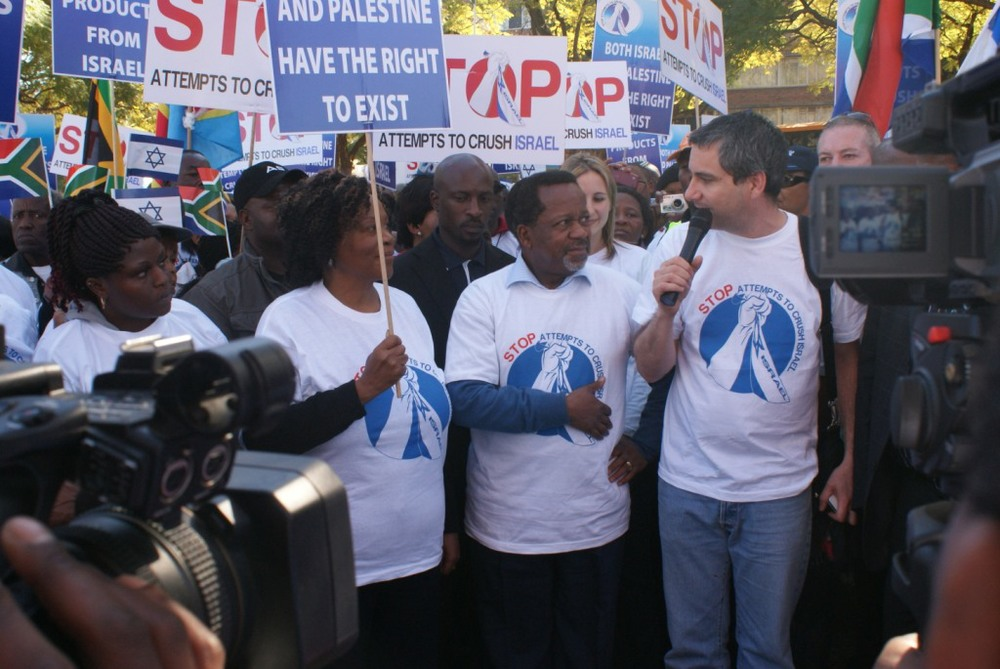 "Click photo to download. Caption: Ben Swartz of the South African Zionist Federation (with microphone) thanks Reverend Kenneth Meshoe (second from right), a parliament member in South Africa, for his efforts on behalf of the Jewish community at last June's ""Africans for Israel"" march. Credit: Courtesy Esther Meshoe."