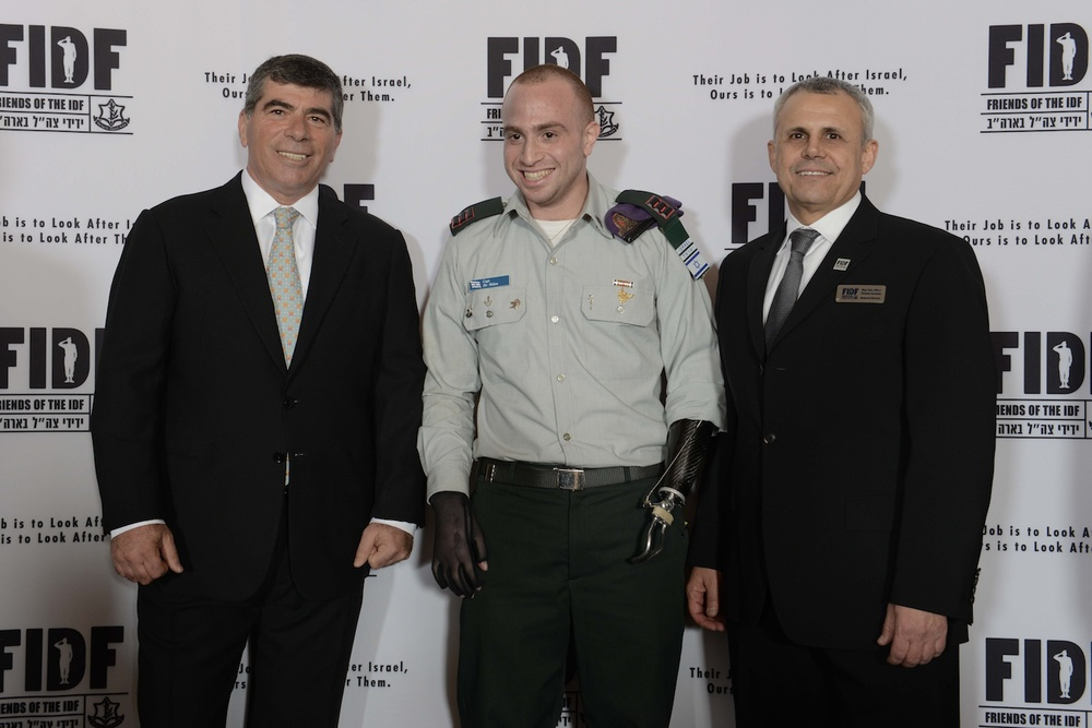 Click photo to download. Caption: IDF captain Ziv Shilon (center), who has one prosthetic hand and is paralyzed in the other,  poses with former IDF Chief of Staff Lt. Gen. (Res.) Gabi Ashkenazi (left) and Friends of the Israel Defense Forces National Director Maj. Gen. Yitzhak (Jerry) Gershon at FIDF's national gala in New York this March. Credit: Shahar Azran.
