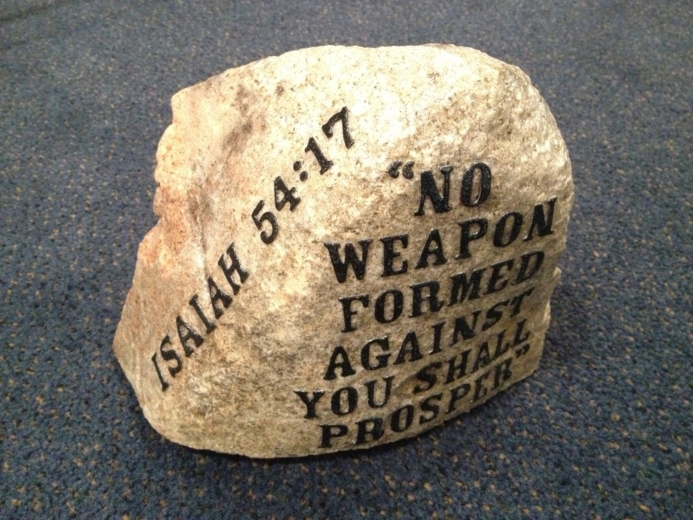 "Click photo to download. Caption: The rock thrown through the windows of Victory Assembly of God Church in Sharon, Mass., last month has been repurposed as a symbol of hope, inscribed with the words of Isaiah 54:17, ""No weapon forged against you shall prosper."" Credit: Victory Assembly of God Church."