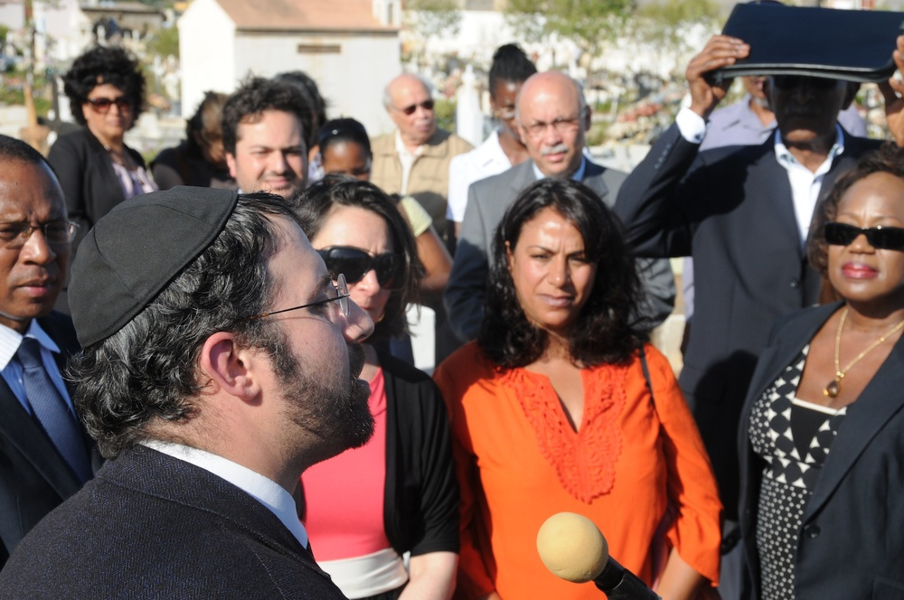 Click photo to download. Caption: Lisbon's Chief Rabbi Eliezer Shai di Martino offered prayers during the rededication ceremony of the Jewish burial site in Praia, Cape Verde. The islands are a former Portuguese colony. U.S. Ambassador to Cape Verde Adrienne O'Neal is to the far right; the French and Portuguese ambassadors were also present. Credit: Cape Verde Jewish Heritage Project, Inc.