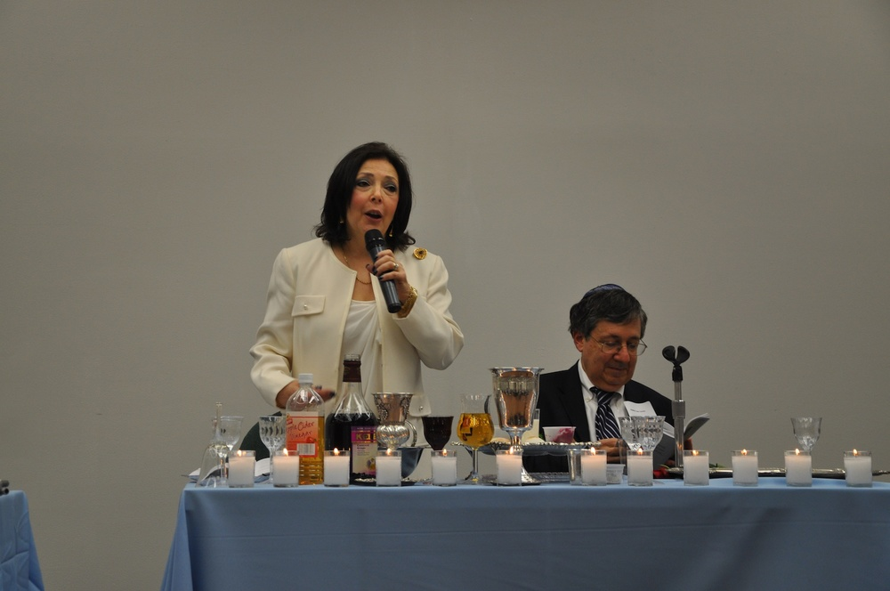 Click photo to download. Caption: Barbara Wind, director of the Holocaust Council of Metrowest, speaks at the first Holocaust seder, an idea she initiated, in Whippany, NJ, on May 19. Next to her is Rabbi Len Levin of South Orange, the seder leader. Credit: Michele Alperin.