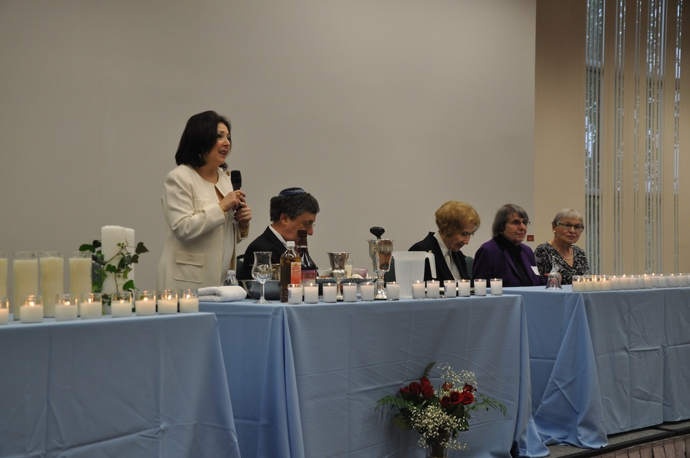 Click photo to download. Caption: The dais at the first Holocaust seder in Whippany, NJ, on May 19. Speaking is Barbara Wind, director of the Holocaust Council of Metrowest, who initiated the idea for the seder. Credit: Michele Alperin.