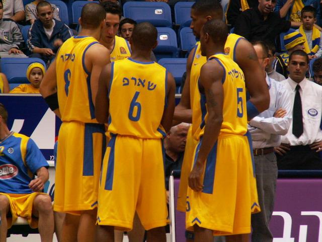 Caption: Basketball players from Maccabi Tel Aviv huddle up.