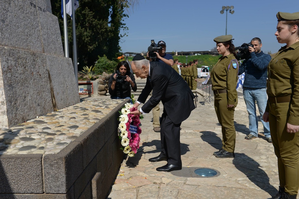 Click photo to download. Caption: Israeli President Shimon Peres places flowers on the grave of early Zionist activist Yosef Trumpeldor in Tel Hai, Israel on Feb. 21, 2013. Credit: Mark Neyman/GPO/Flash90.