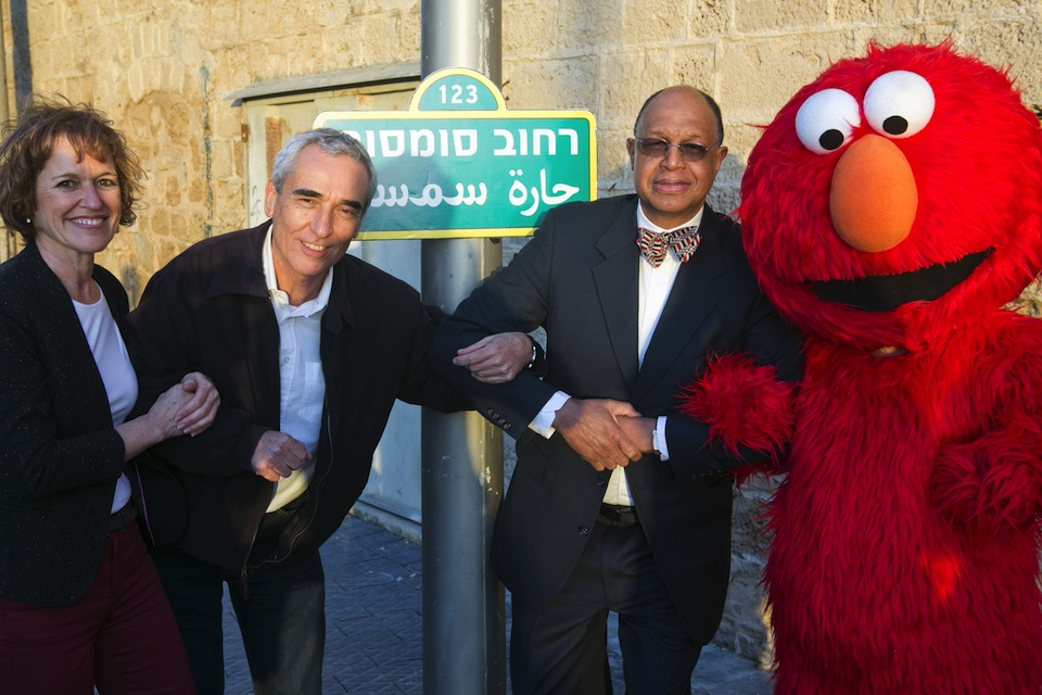 Click photo to download. Caption: From left to right, Alona Abt (Rehov Sumsum's director on its set in Herzliya), Tamir Paul, Melvin Ming (president and CEO of Sesame Workshop), and Elmo, in front of the Rehov Sumsum (Sesame Street) sign in Israel. Credit: D Guthrie.