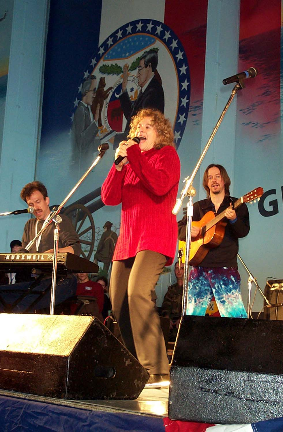 Click photo to download. Caption: Carole King, accompanied by Jon Carroll on the keyboard, and Arlen Schierbaum on the guitar, sings for about 1,500 sailors and Marines aboard the USS Harry S. Truman in the Mediterranean. Credit: Linda D. Kozaryn.