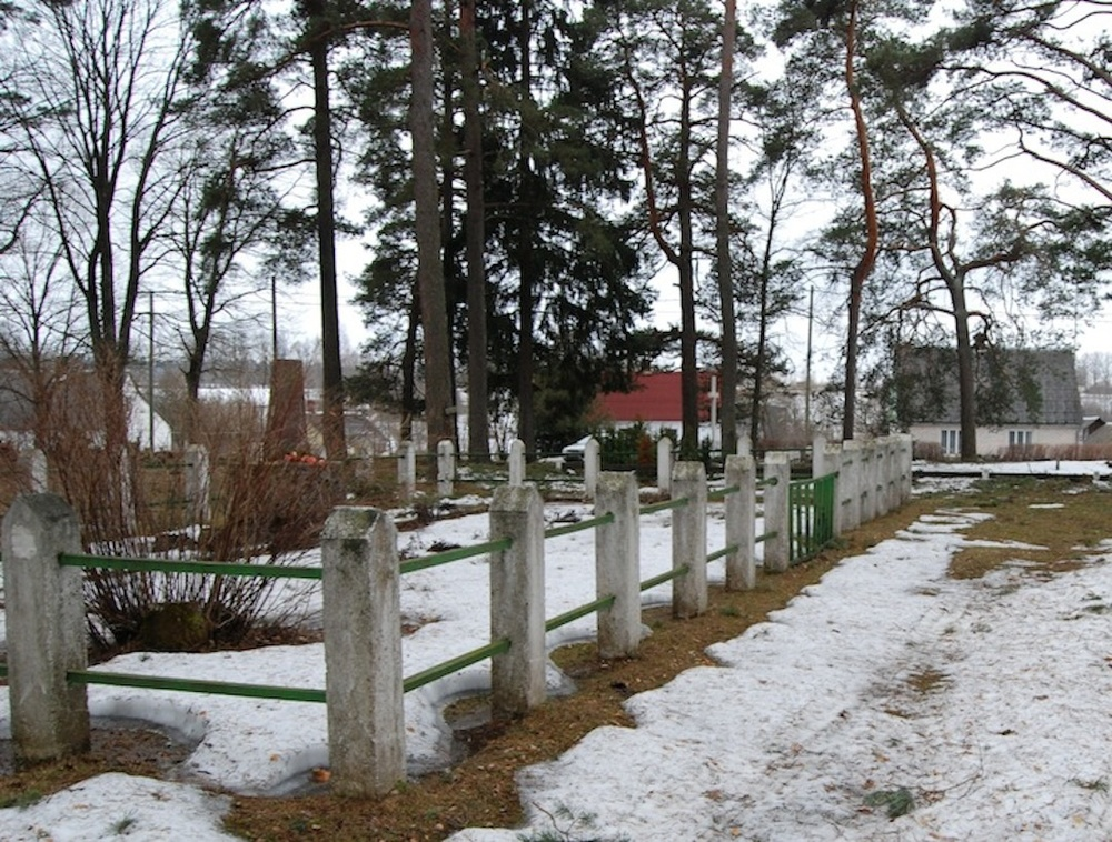 Click photo to download. Caption: The Jews of Akniste, murdered in a mass shooting, are buried in the enclosed space. The cross, only 10 feet from this site, marks the grave of those who murdered them. Credit: Courtesy of Eugene Levin.