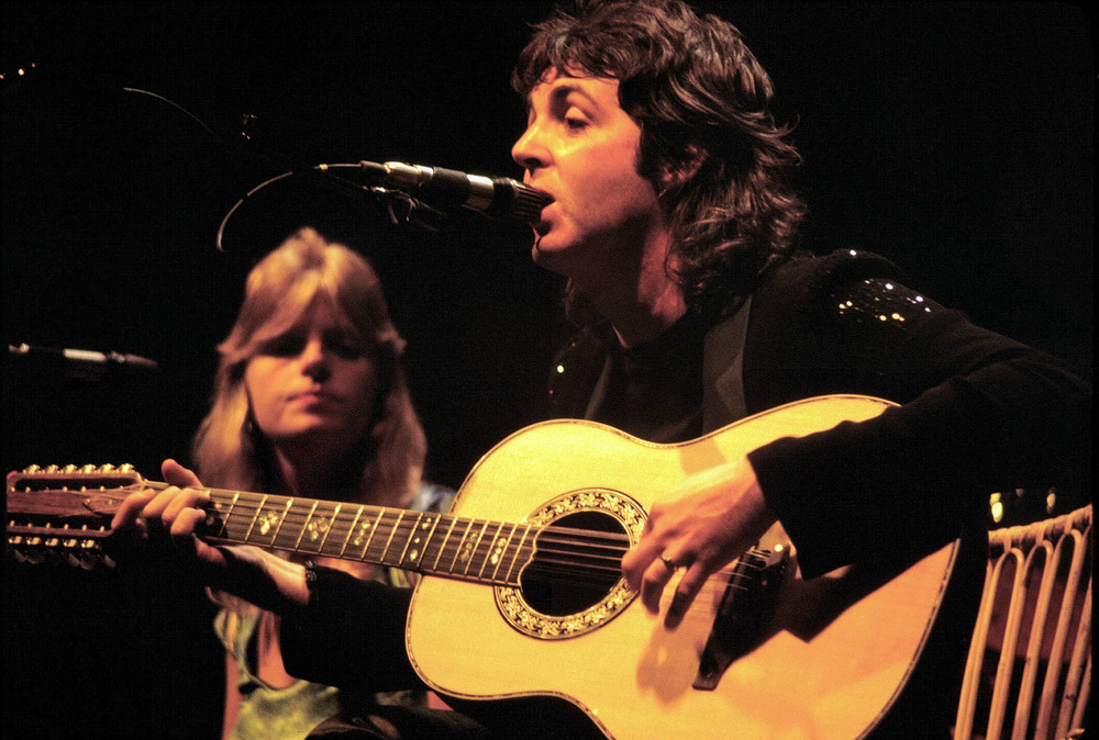 "Click photo to download. Caption: Paul McCartney performs in 1976, with his wife Linda in the background. McCartney sings ""Man, I was mean, but I'm changing my scene and I'm doing the best that I can"" in ""Getting Better,"" No. 3 on the JNS.org High Holidays playlist. Credit: Jim Summaria via Wikimedia Commons."