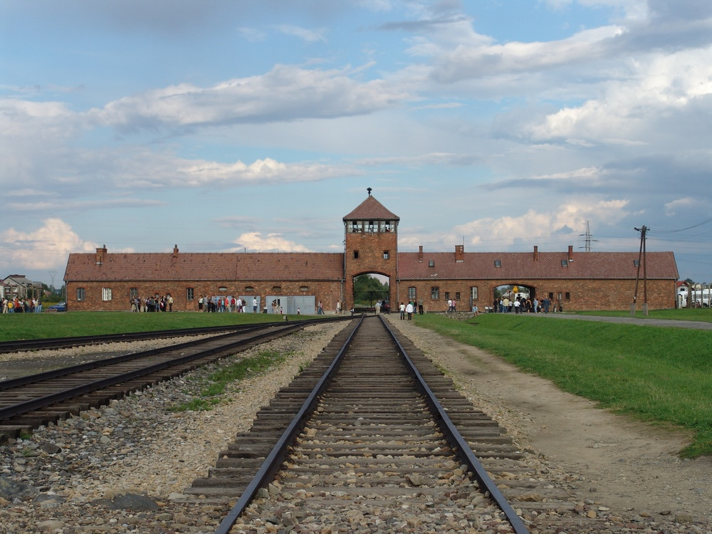 Click photo to download. Caption: The main gate of the Auschwitz-Birkenau concentration camp, which was among the places where Yom Kippur was observed in the shadow of death by Jews during the Holocaust. Credit: Angelo Celedon via Wikimedia Commons.