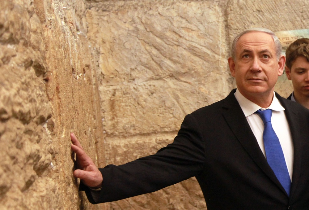 "Click photo to download. Caption: Israeli Prime Minister Benjamin Netanyahu seen at the Western Wall on January 22, 2013. Netanyahu's latest role at the Western Wall comes as a tour guide, as seen on Peter Greenberg's travel show, ""The Royal Tour,"" which follows various heads of state as they serve as tour guides in their native countries. Credit: Marc Israel Sellem/POOL/FLASH90."