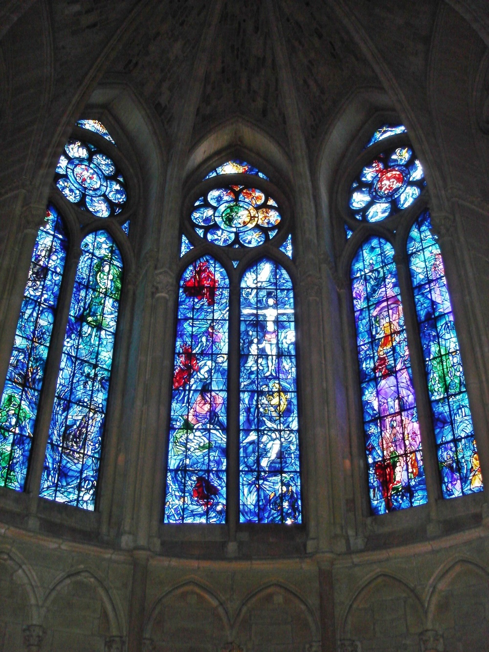 Click photo to download. Caption: Stained-glass windows in the axial chapel of Reims Cathedral in France, designed by Marc Chagall and made by Charles Marq in 1974. Credit: Peter Lucas via Wikimedia Commons.
