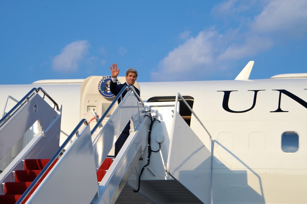 "Click photo to download. Caption: U.S. Secretary of State John Kerry waves as he boards his plane at Andrews Air Force Base for a flight to Amman, Jordan, on July 15, 2013. On that trip to Jordan, Kerry said Arab ministers told him that the core issue of instability in this region and in many other parts of the world is the Palestinian-Israeli conflict."" Credit: U.S. Department of State."